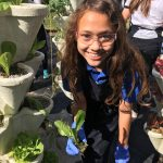 girl planting showing off plant produced by hydroponics